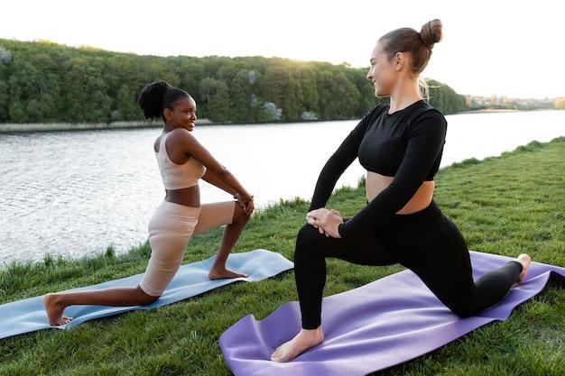 Mulheres jovens em roupas esportivas malhando ao ar livre