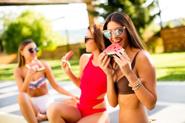 Mulheres jovens, em, swimsuit, comendo melancia, por, piscina, em, dia quente verão