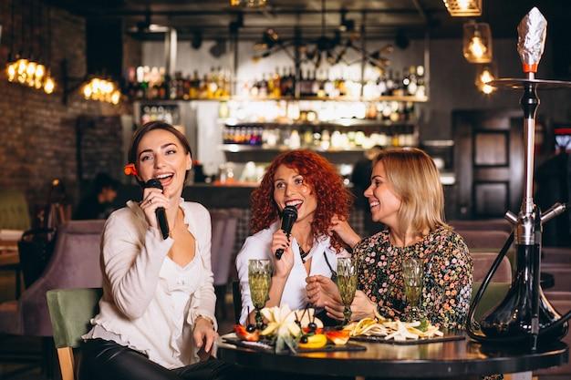 Mulheres jovens, em, um, barra, cantando, karaoke