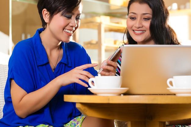 Mulheres jovens em um coffeeshop asiático