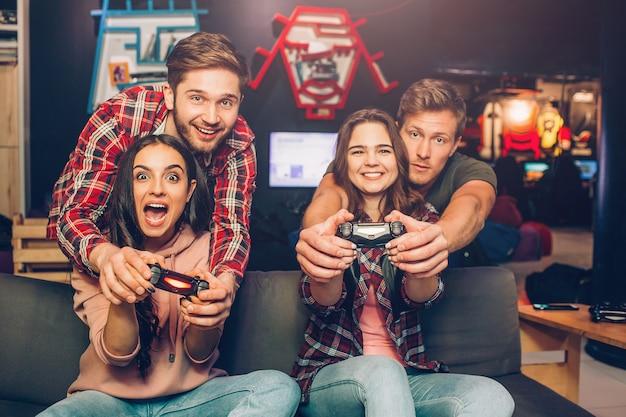 Mulheres jovens emocionais sentam-se no sofá na sala de jogos. eles seguram gamepads e jogam. caras ajudem eles.