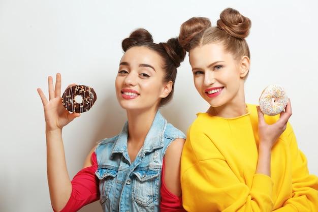 Mulheres jovens engraçadas com rosquinhas saborosas na superfície branca
