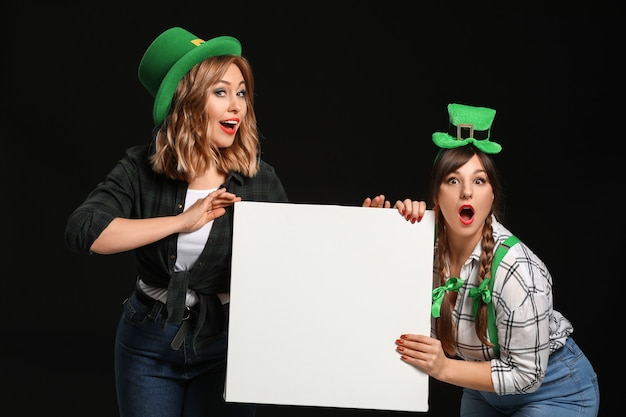 Mulheres jovens engraçadas com um cartaz em branco no escuro. comemoração do dia de são patrício
