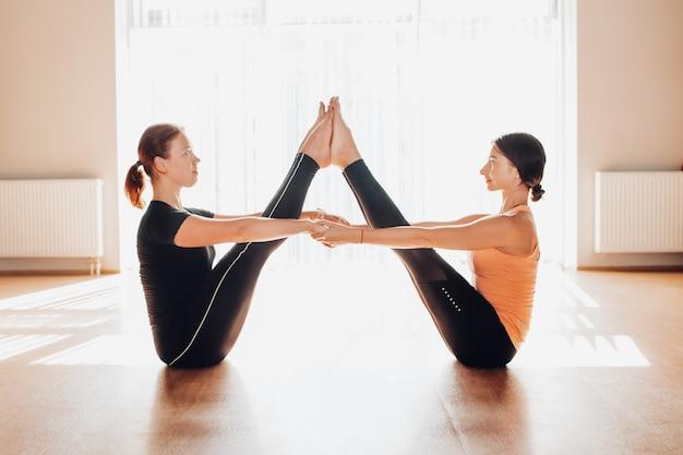Mulheres jovens, equilibrando e praticando ioga em um estúdio de luz