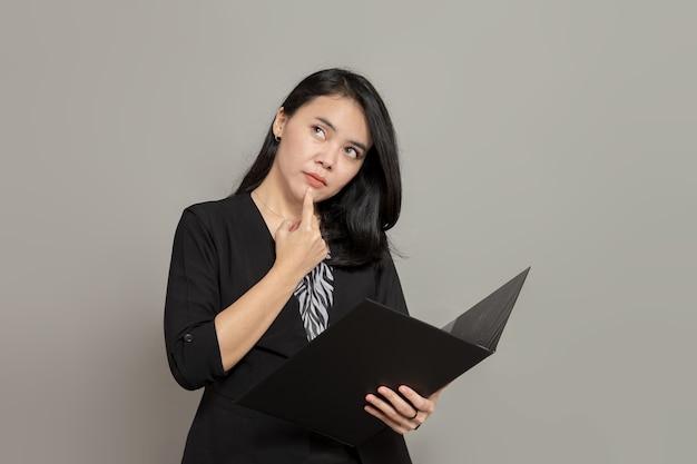 Mulheres jovens estão imaginando ou procurando ideias enquanto seguram uma pasta