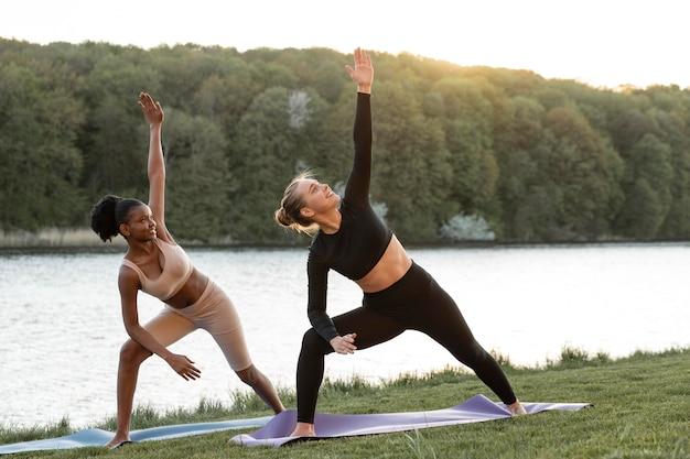 Mulheres jovens fazendo exercícios ao ar livre juntas