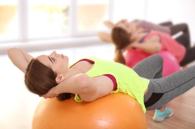 Mulheres jovens fazendo exercícios com bola