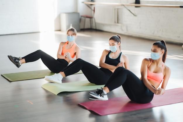 Mulheres jovens fazendo exercícios de flexão na sala durante a manhã. meninas magras usando máscaras para proteger a pandemia da doença covid-19 e o distanciamento social.
