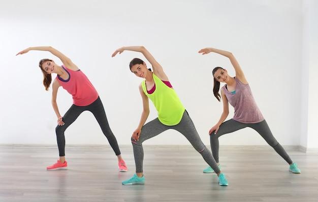 Mulheres jovens fazendo exercícios na academia