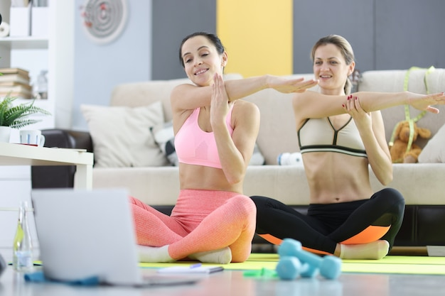 Mulheres jovens fazendo ioga na frente da tela do laptop