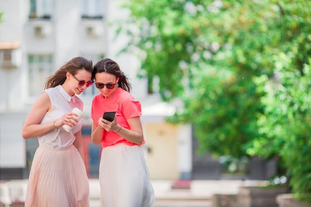 Mulheres jovens felizes andando pela rua da cidade.