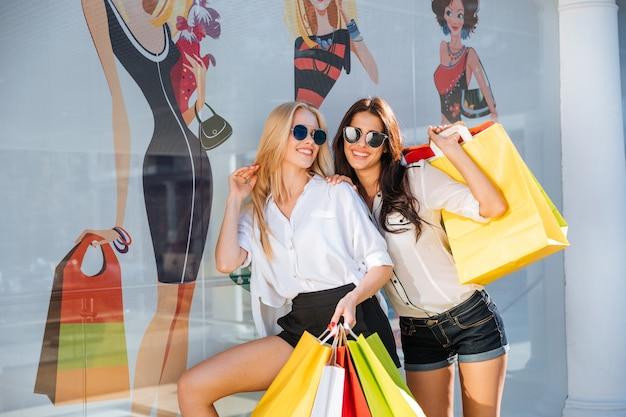 Mulheres jovens felizes com sacolas de compras, andando na rua e se divertindo