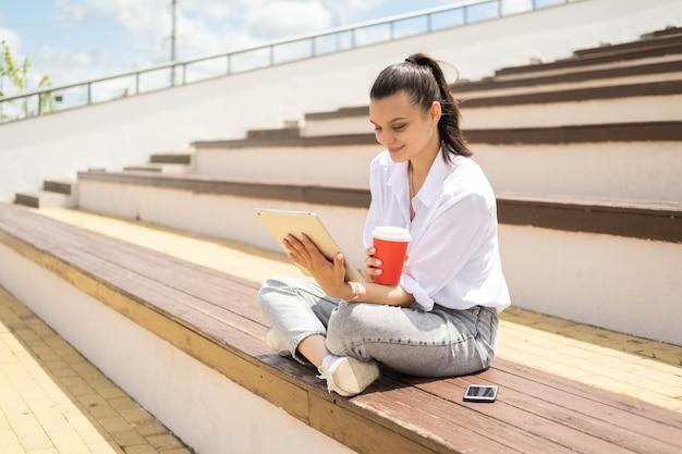 Mulheres jovens felizes com tablet segurando o copo de papel de café, aproveitando o dia de sol sentado no anfiteatro.
