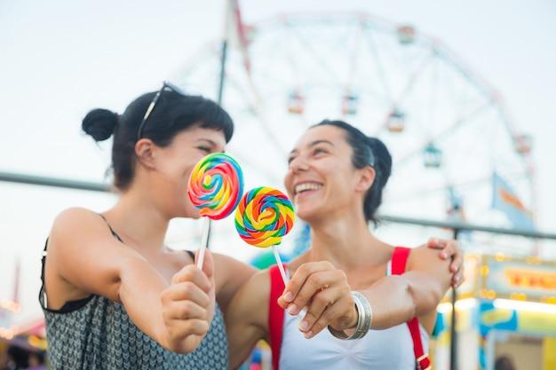 Mulheres jovens felizes comendo pirulito