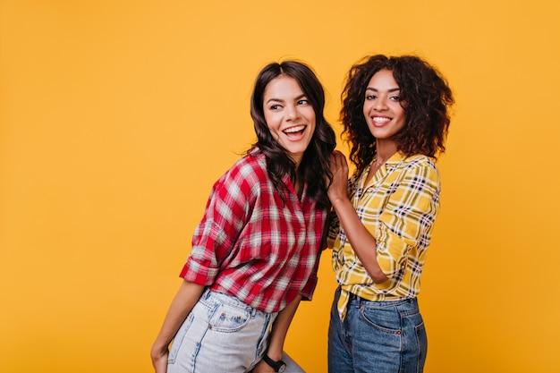 Mulheres jovens felizes dançando. retrato dentro de casa de duas meninas elegantes em jeans.