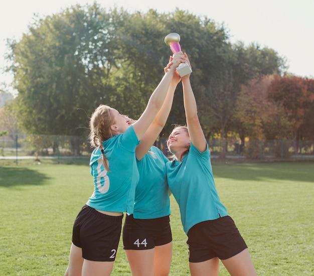 Mulheres jovens felizes, levantando um troféu