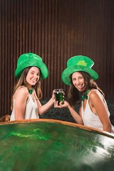 Mulheres jovens felizes segurando o copo de bebida no sofá perto de mesa