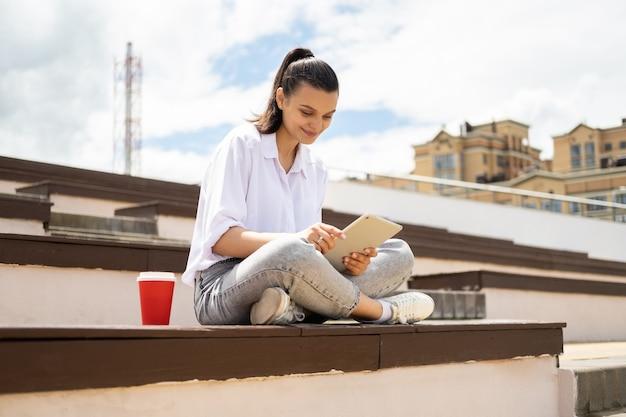 Mulheres jovens felizes segurando um tablet com um copo de papel de café, aproveitando o dia de sol, sentadas nas escadas da cidade Foto Premium