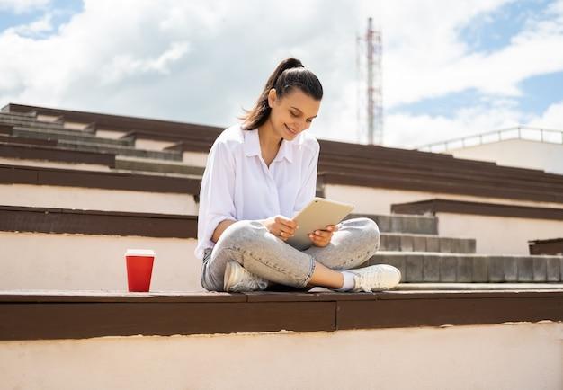 Mulheres jovens felizes segurando um tablet segurando um copo de papel de café, aproveitando o dia de sol sentado na cidade