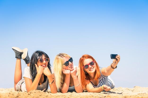 Mulheres jovens felizes tomando selfie na praia