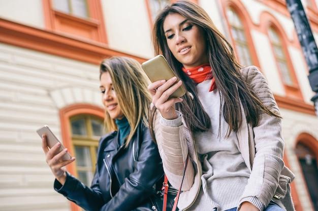 Mulheres jovens, ficar, em, um, urbano, área, usando, telefone móvel, cidade