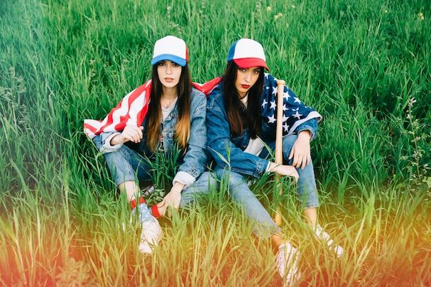 Mulheres jovens graves com bandeira americana sentado na grama
