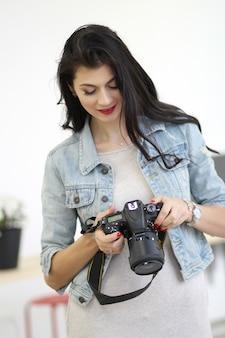Mulheres jovens, mantendo a câmera profissional nas mãos