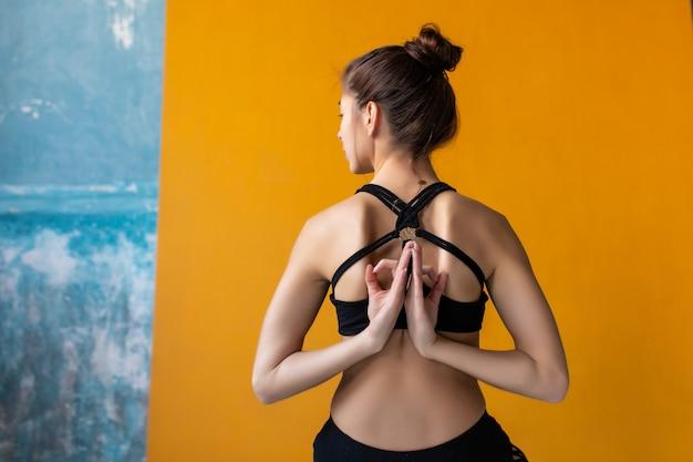 Mulheres jovens, meditando com sinal de jnana mudra na aula de yoga