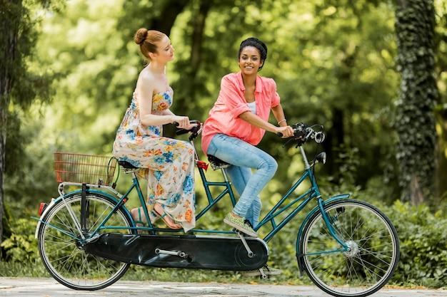 Mulheres jovens, montando, ligado, a, bicicleta tandem