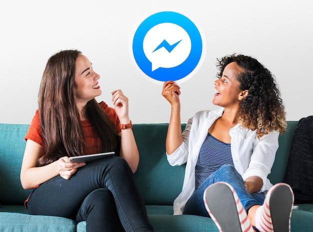 Mulheres jovens mostrando um ícone do facebook messenger