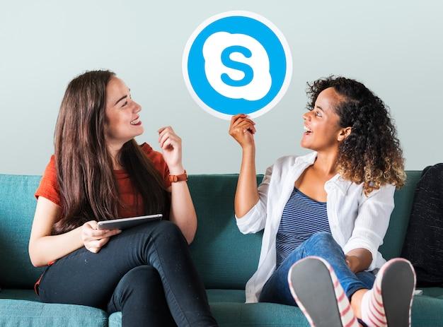 Mulheres jovens, mostrando, um, skype, ícone