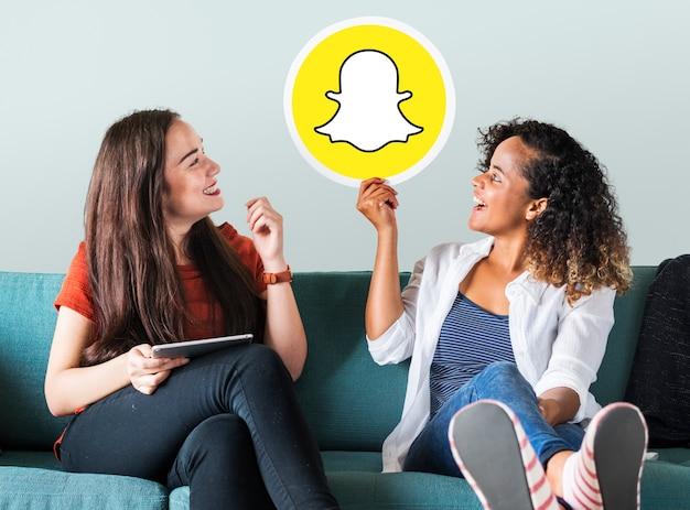 Mulheres jovens, mostrando, um, snapchat, ícone