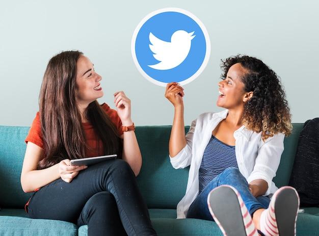 Mulheres jovens, mostrando, um, twitter, ícone