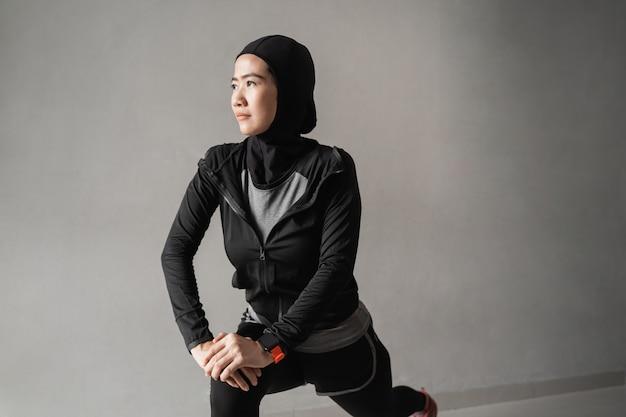 Mulheres jovens muçulmanas vestindo sportswear hijab fazendo alongamento