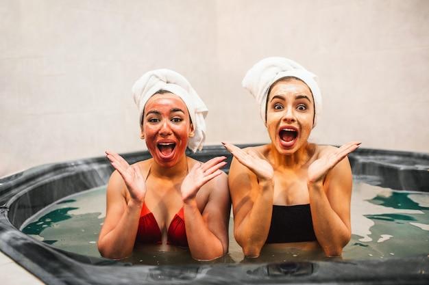 Mulheres jovens muito felizes sentam-se no banho de hidromassagem cheio de água e olham. eles são surpreendidos e adorados. os modelos têm máscaras de beleza no rosto.