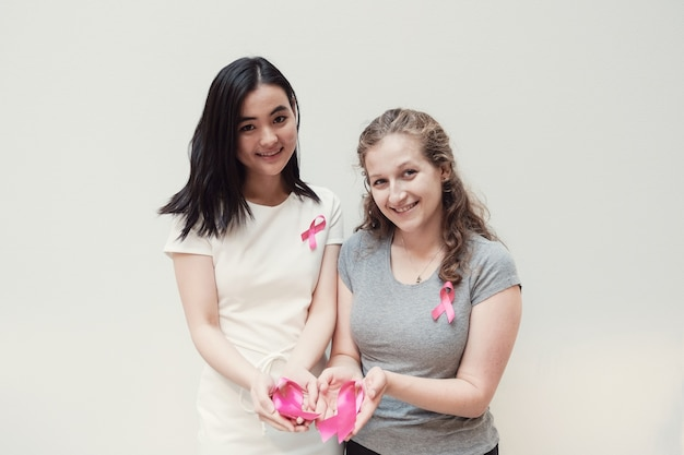 Mulheres jovens multiculturais com fitas cor de rosa, conscientização do câncer de mama
