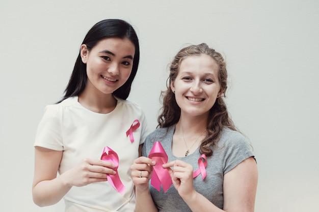 Mulheres jovens multiculturais com fitas cor de rosa