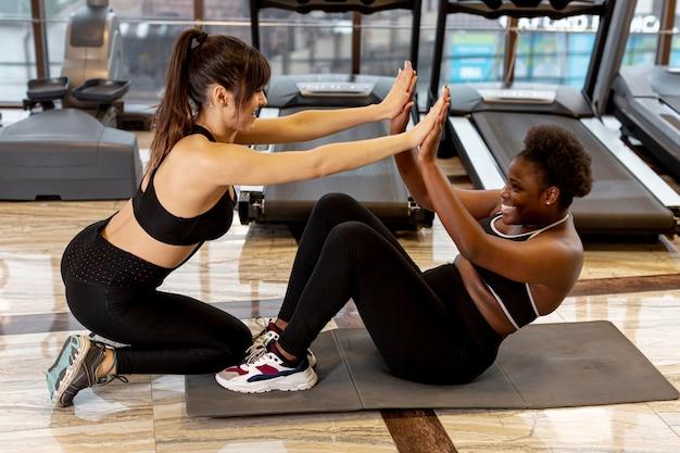 Mulheres jovens na academia trabalhando juntos