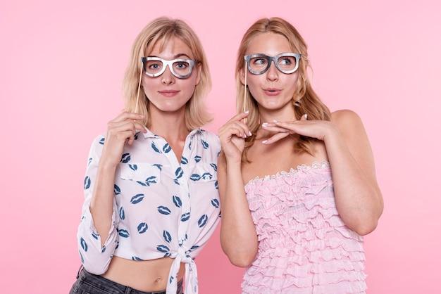 Mulheres jovens na festa tirando fotos com máscara de óculos