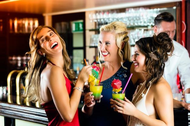 Mulheres jovens no bar ou clube se divertindo e rindo