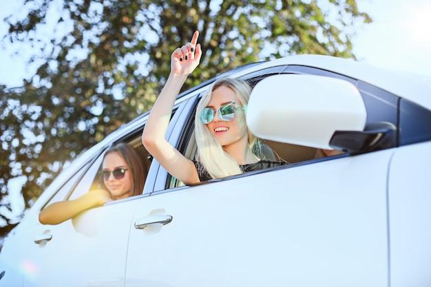 Mulheres jovens no carro sorrindo