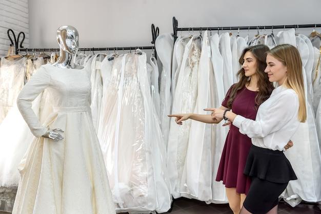 Mulheres jovens no salão de casamento escolhendo o vestido