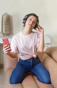 Mulheres jovens ouvindo música com fones de ouvido e celular nas mãos enquanto estão sentadas no sofá bege de casa