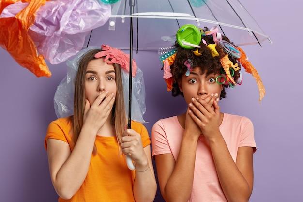 Mulheres jovens posando com lixo plástico