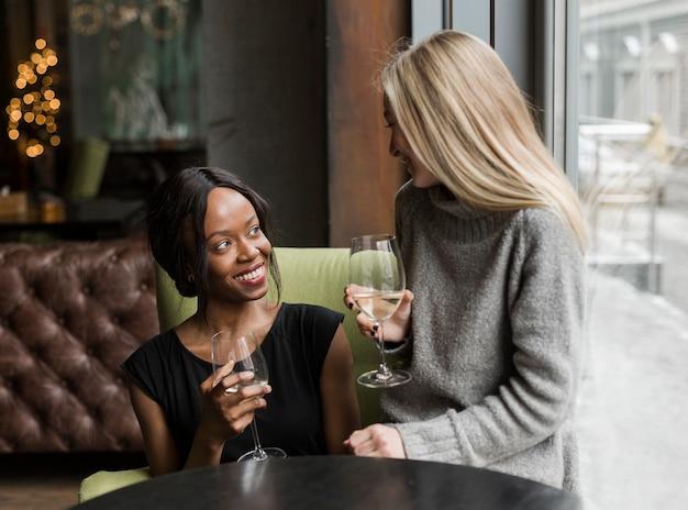 Mulheres jovens positivas, desfrutando de um copo de vinho