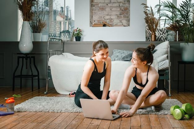 Mulheres jovens praticam esportes em casa, malham online