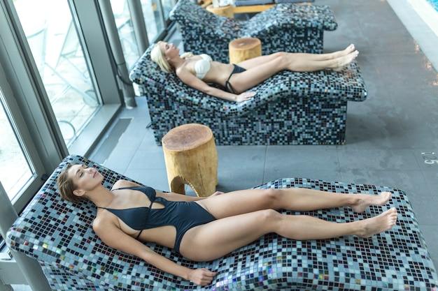 Mulheres jovens relaxantes na sauna a vapor. mulheres com corpo esguio e pele saudável descansando e realizando procedimentos de spa no hammam ou banho turco