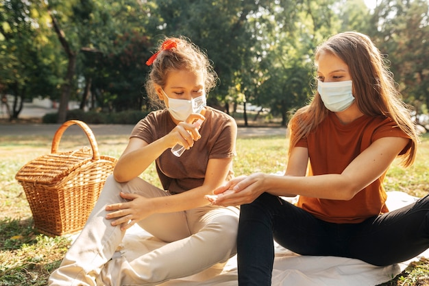 Mulheres jovens se desinfetando antes de fazer um piquenique