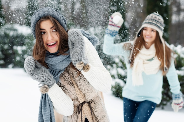 Mulheres jovens se divertem durante a luta de bolas de neve