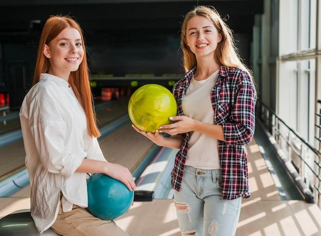 Mulheres jovens segurando bolas de boliche coloridas